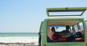 Vista posterior de los pares que se sientan en una furgoneta 4k almacen de video