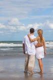 Vista posterior de los pares románticos del hombre y de la mujer en una playa Imágenes de archivo libres de regalías