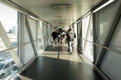 Vista posterior de los pasajeros en el puente del aeropuerto, puente de una línea aérea del jet donde los pasajeros conectan con  foto de archivo