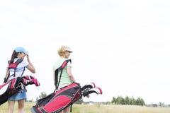 Vista posterior de mujeres con los bolsos de club de golf en el curso contra el cielo claro Fotografía de archivo