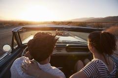 Vista posterior de pares en el viaje por carretera que conduce el coche convertible clásico hacia puesta del sol imagen de archivo