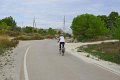 Vista posterior de un ciclista en el campo Imagen de archivo libre de regalías