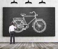 Vista posterior de un hombre de negocios en ropa formal que está dibujando un bosquejo de una bicicleta en la pizarra negra enorm Foto de archivo