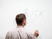 Vista posterior de un hombre de negocios que escribe el riesgo de la palabra Imagen de archivo
