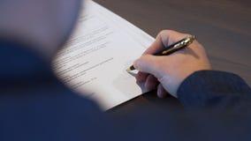 Vista posterior de un hombre de negocios en contrato de firma de la camisa negra existencias Hombre que pone su firma en el docum imagenes de archivo