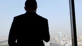 Vista posterior de un hombre de negocios en la situación del traje con su smartphone a disposición, mirando fuera de la ventana e almacen de video