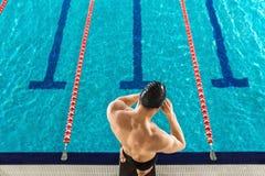 Vista posterior de un hombre que prepara gafas de la natación fotos de archivo libres de regalías