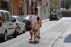 Vista posterior de un montar a caballo de los pares en una bicicleta en la calle de Calella Fotografía de archivo