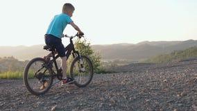 Vista posterior de un muchacho que monta una bici negra en un área montañosa Ciclo del niño Muchacho joven que monta una bici en  almacen de video