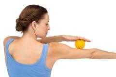Vista posterior de una bola de la tensión de la tenencia de la mujer joven en el brazo Imagen de archivo