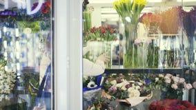 Vista posterior de una dependienta que pone los floreros en una ventana de la floristería almacen de metraje de vídeo