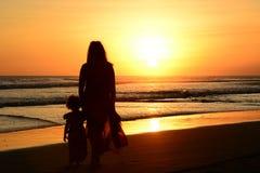 Vista posterior de una madre y de una hija que se colocan en la playa imagen de archivo libre de regalías