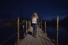 Vista posterior de una muchacha con la mochila que camina a lo largo del puente pontón Iluminación de la noche El caminar y conce Imagen de archivo