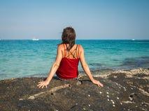 Vista posterior de una mujer caucásica que se sienta en una playa tropical imagen de archivo libre de regalías