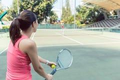 Vista posterior de una mujer joven del ajuste que juega a tenis en una corte profesional fotos de archivo