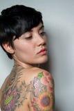 Vista posterior de una mujer morena del cortocircuito-pelo hermoso con un tatuaje Fotos de archivo libres de regalías