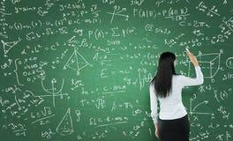 Vista posterior de una mujer pensativa que está escribiendo cálculos de la matemáticas en el tablero de tiza verde fotografía de archivo libre de regalías