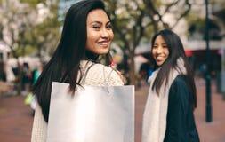 Vista posterior de una mujer que lleva un bolso que hace compras foto de archivo libre de regalías