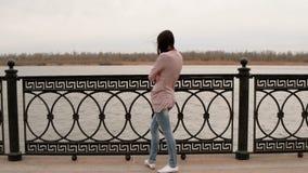 Vista posterior de vaqueros y de una chaqueta casuales pensativos de Weared de la mujer joven que hacen frente en el río 4K metrajes