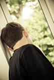 Vista posterior del adolescente que mira hacia fuera la ventana Foto de archivo libre de regalías
