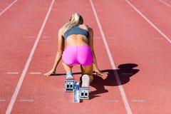 Vista posterior del atleta de sexo femenino lista para correr en pista corriente Imagen de archivo