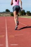Vista posterior del atleta de sexo femenino que corre en la pista corriente Imagenes de archivo