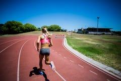Vista posterior del atleta de sexo femenino que corre en la pista que compite con Fotos de archivo