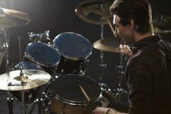 Vista posterior del batería Playing Drum Kit In Studio Imágenes de archivo libres de regalías