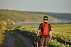 Vista posterior del ciclista joven con el ciclista de la montaña en el prado del verano Fotos de archivo libres de regalías