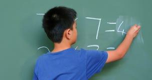 Vista posterior del colegial asiático que soluciona el problema de matemáticas en la pizarra en sala de clase en la escuela 4k almacen de video