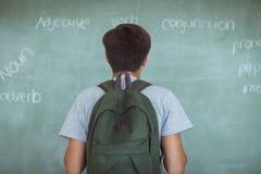 Vista posterior del colegial con la pizarra de la lectura de la mochila en sala de clase Imagen de archivo libre de regalías