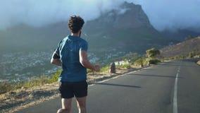 Vista posterior del corredor masculino del atleta que corre en el camino de la montaña almacen de metraje de vídeo