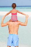 Vista posterior del día de fiesta de la playa de Carrying Daughter On del padre imagen de archivo
