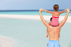 Vista posterior del día de fiesta de la playa de Carrying Daughter On del padre Foto de archivo libre de regalías