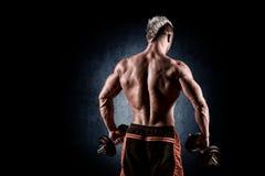 Vista posterior del entrenamiento del culturista con pesas de gimnasia en backgr negro Imagen de archivo