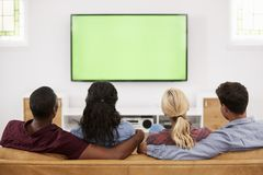 Vista posterior del grupo de amigos jovenes que miran la televisión junto Fotos de archivo