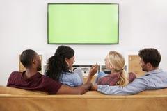 Vista posterior del grupo de amigos jovenes que miran la televisión junto Imagen de archivo libre de regalías