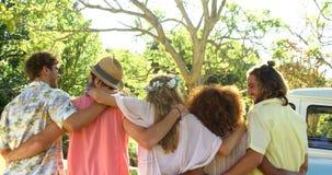 Vista posterior del grupo de brazo que camina de los amigos alrededor almacen de metraje de vídeo