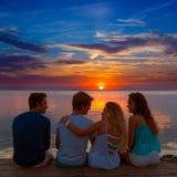 Vista posterior del grupo de los amigos en la diversión de la puesta del sol junto Imagen de archivo