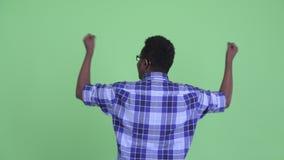 Vista posterior del hombre africano joven feliz del inconformista con los puños aumentados almacen de video