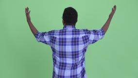 Vista posterior del hombre africano joven feliz del inconformista que mira alrededor almacen de metraje de vídeo