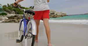 Vista posterior del hombre caucásico que camina con la bicicleta en la playa 4k almacen de metraje de vídeo