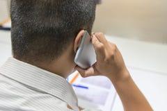 Vista posterior del hombre de la oficina que habla en el teléfono móvil fotografía de archivo libre de regalías