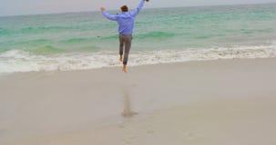 Vista posterior del hombre de negocios caucásico que corre con la chaqueta en la playa 4k almacen de video
