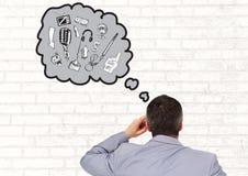Vista posterior del hombre de negocios con la burbuja del pensamiento de diversos gráficos Foto de archivo