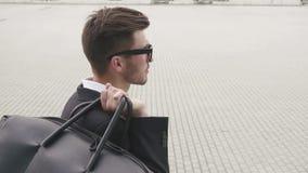 Vista posterior del hombre de negocios hermoso con la maleta Concepto del individuo que viaja almacen de video