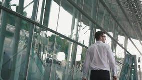 Vista posterior del hombre de negocios hermoso con la maleta en fondo moderno de la pared de cristal del terminal de aeropuerto C almacen de metraje de vídeo