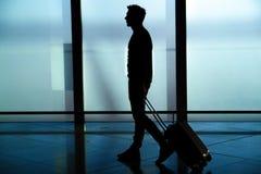 Vista posterior del hombre de negocios que camina con el bolso fuera del aeropuerto Viajero joven que tira de la maleta imagen de archivo libre de regalías