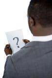 Vista posterior del hombre de negocios que lleva a cabo una muestra del signo de interrogación Fotografía de archivo