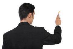 Vista posterior del hombre de negocios que señala en el copyspace con la pluma, aislante Fotografía de archivo